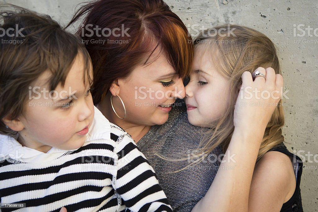 Mother Cuddling With Her Two Children, in Outdoor Setting royalty-free stock photo