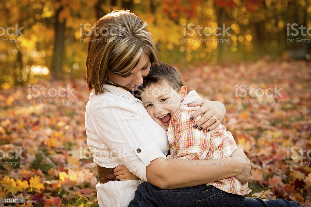Mother Cuddling With Little Son While Outside on Fall Day royalty-free stock photo