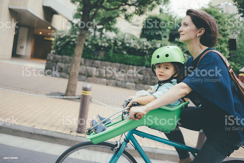Mother cycling with her child in city, Tokyo stock photo