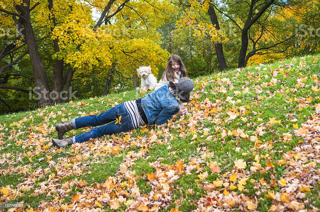 Mother, daughter and dog having fun in autumn leaves royalty-free stock photo