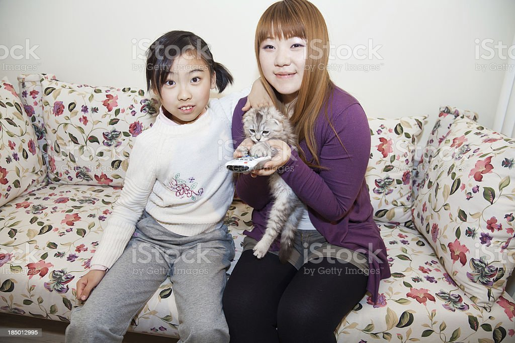 Mother, daughter and the kitten watching TV in living room stock photo