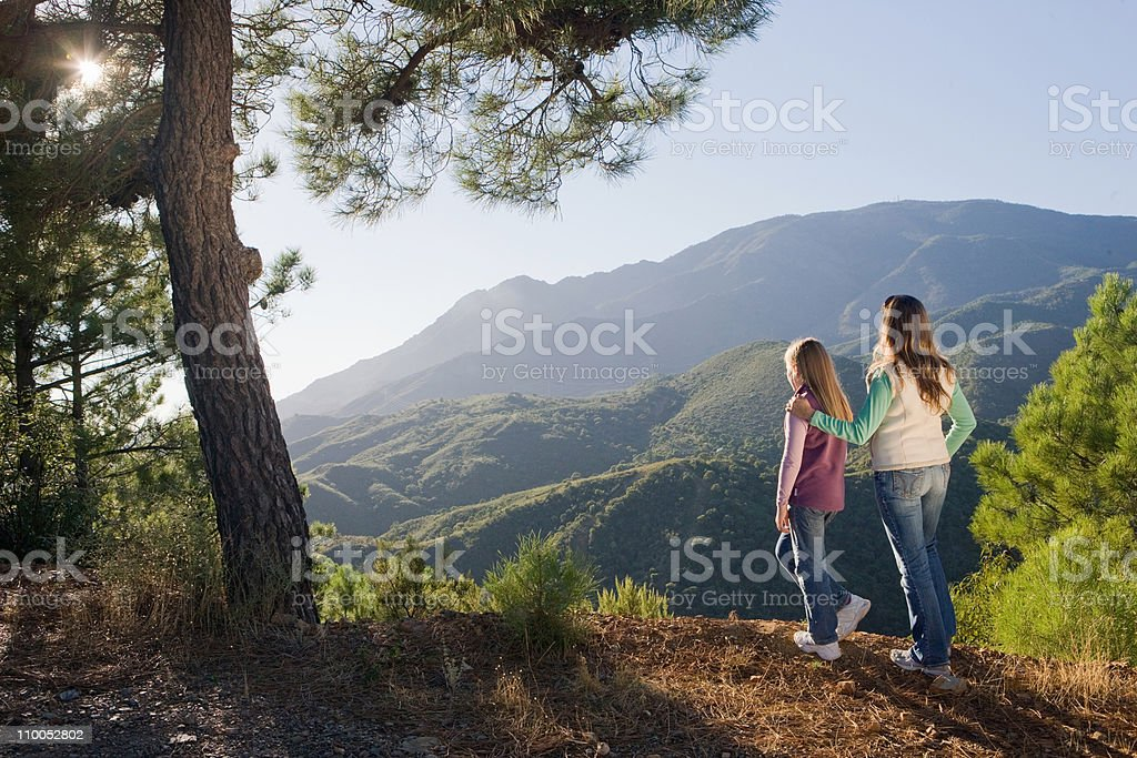 Mother & daughter overlooking mountains stock photo