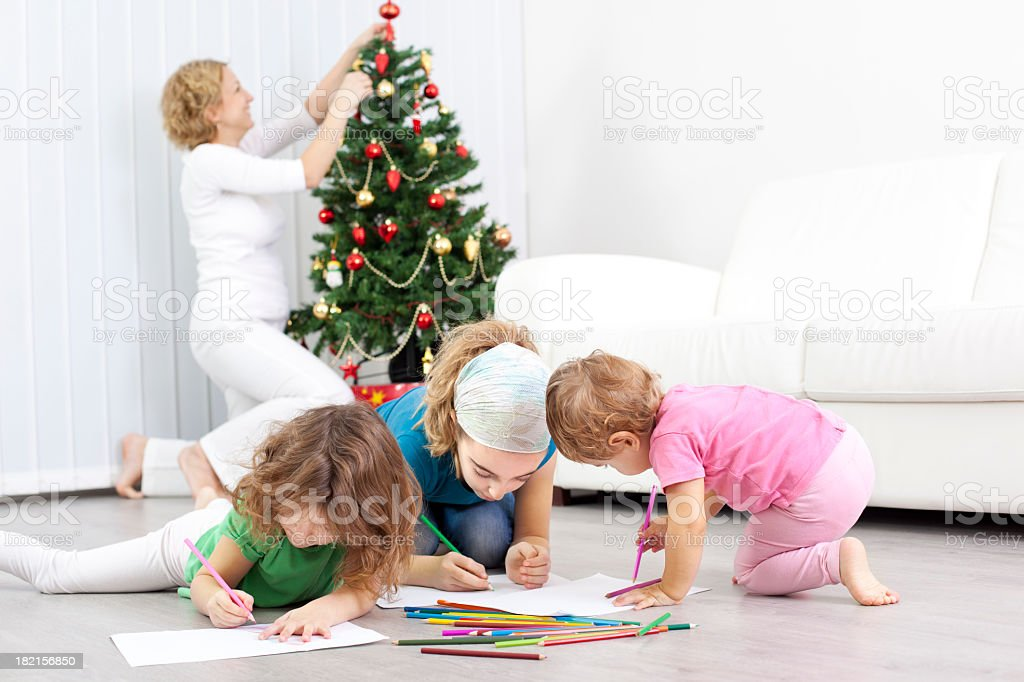 Mother decorating Christmas Tree and children playing royalty-free stock photo