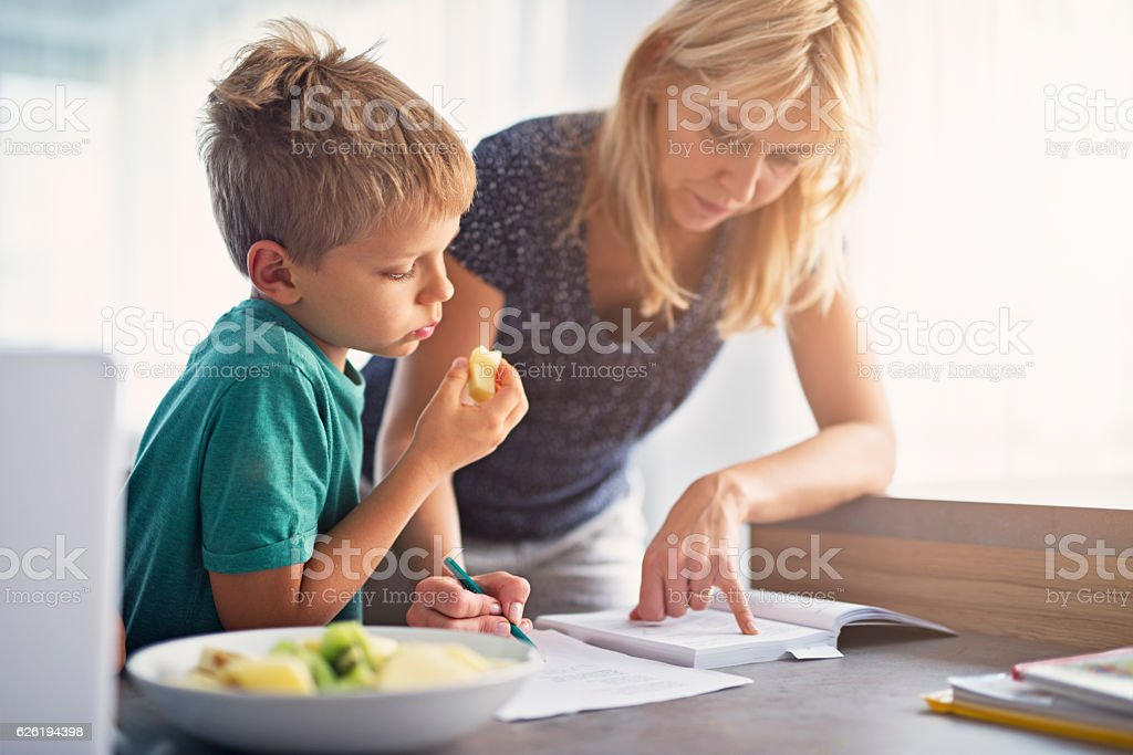 Mother doing homework with her son. stock photo
