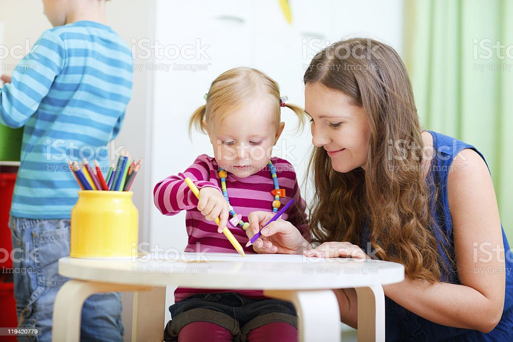 Mother drawing together with her daughter stock photo