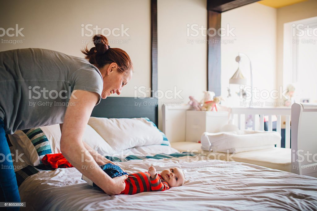 Mother Dressing Baby stock photo