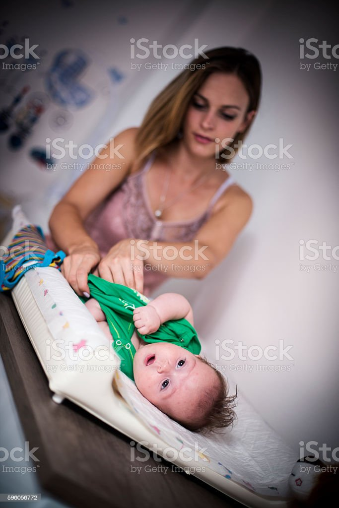 Mother dressing her baby son stock photo