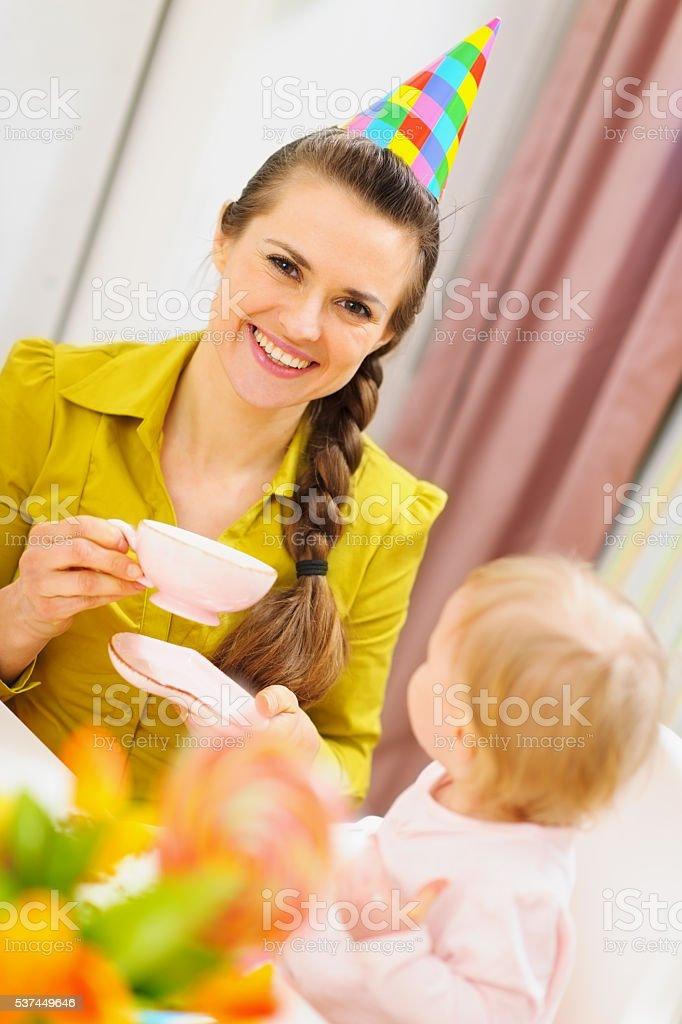mother drinking tea on babies birthday party stock photo