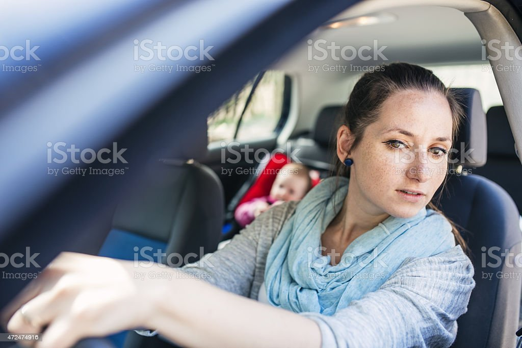 A mother driving and the baby is seating inside the car  stock photo