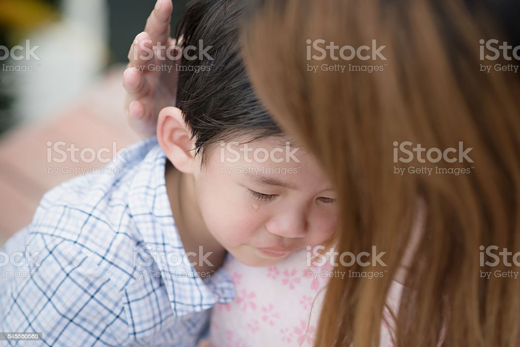 Mother embracing and consoling her son stock photo