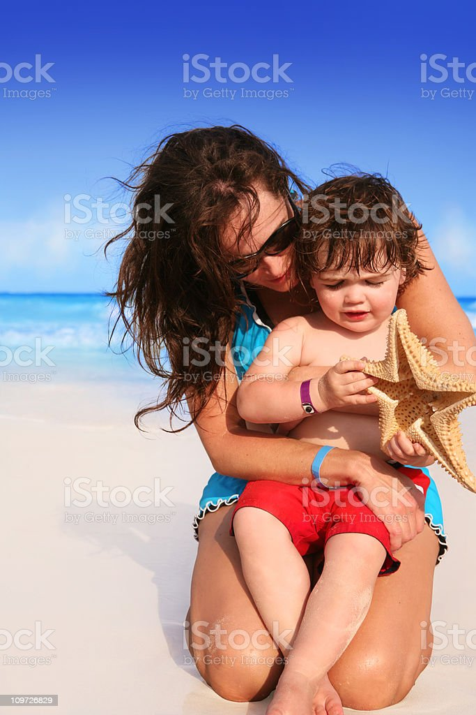 Mother Embracing Child at Tropical Beach stock photo