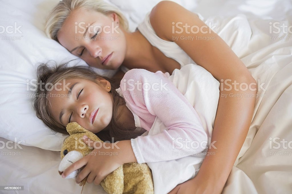 Mother embracing daughter in bed royalty-free stock photo