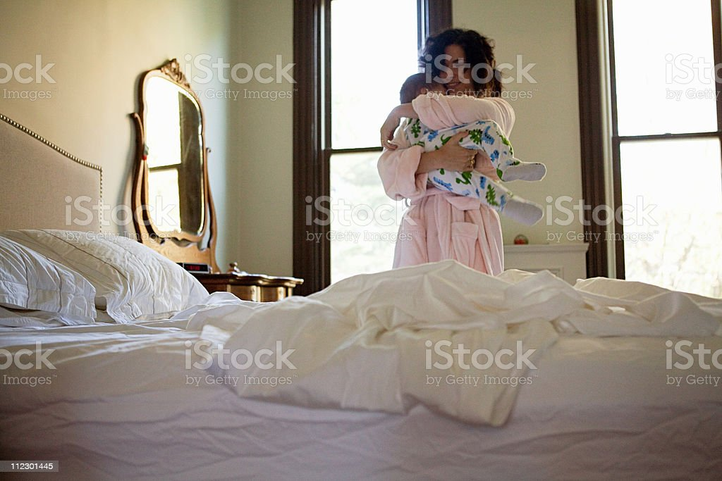 Mother embracing her baby son in bedroom royalty-free stock photo