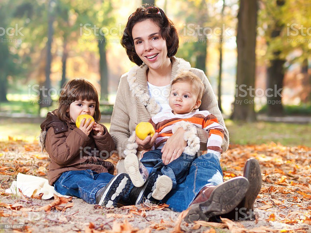 Mother embracing her little children in a autumn park royalty-free stock photo