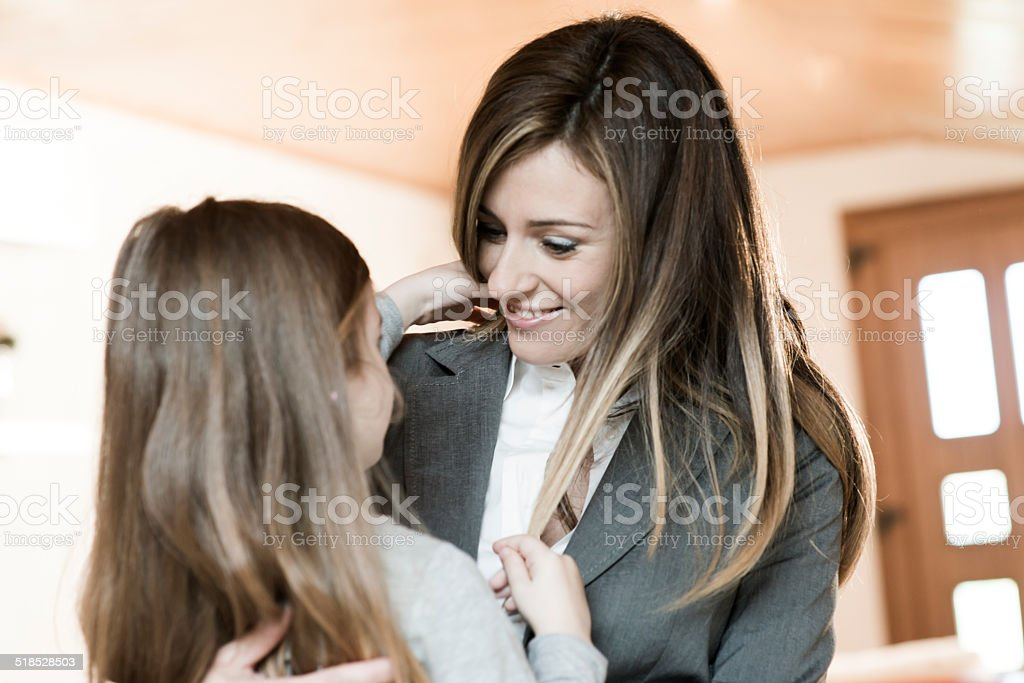 Mother Embracing Her Little Girl Before Leaving To Work stock photo