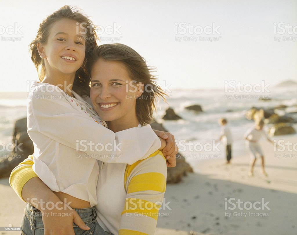 Mother embracing young daughter on a beach royalty-free stock photo