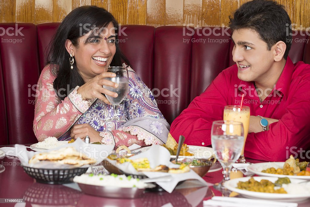 Mother enjoying dinner with her son at indian restaurant royalty-free stock photo