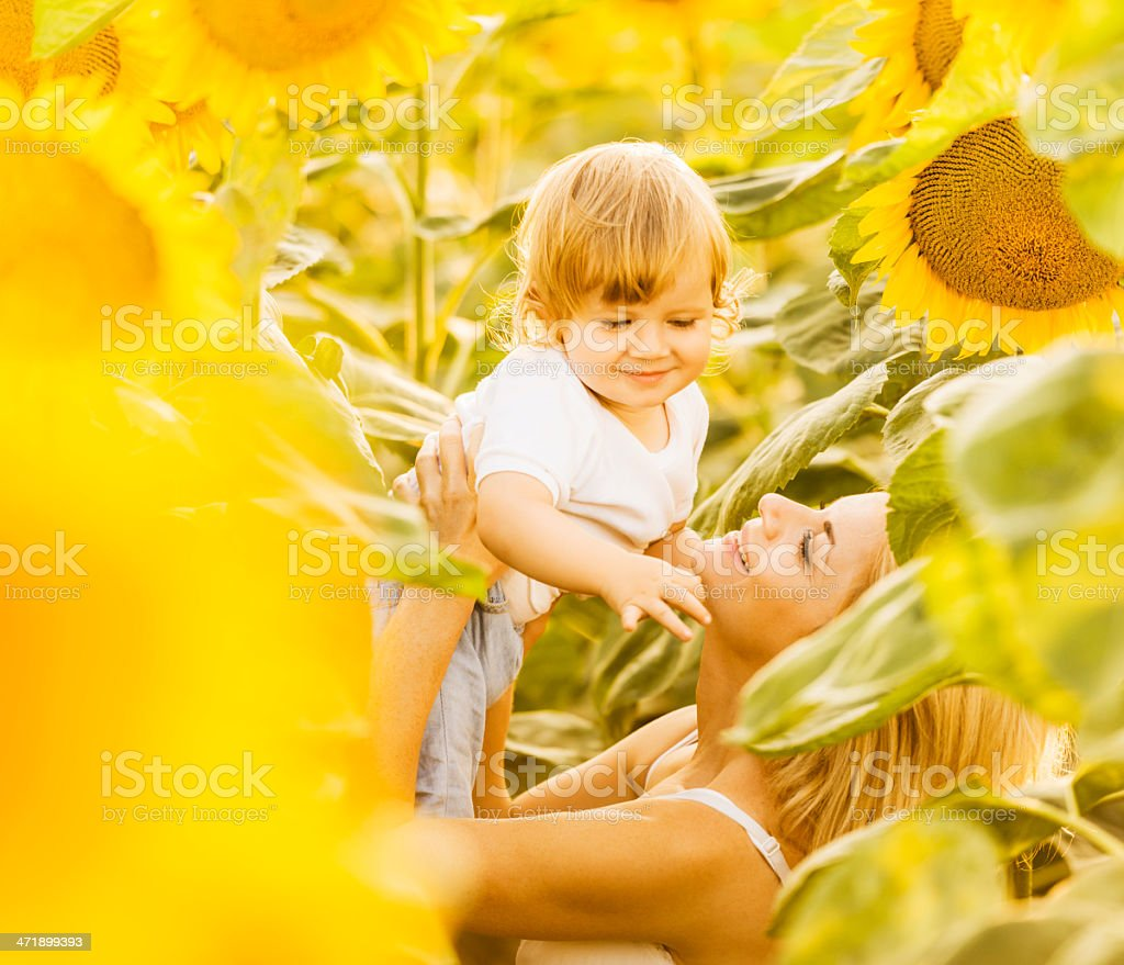 Mother enjoying with her son among sunflowers. royalty-free stock photo