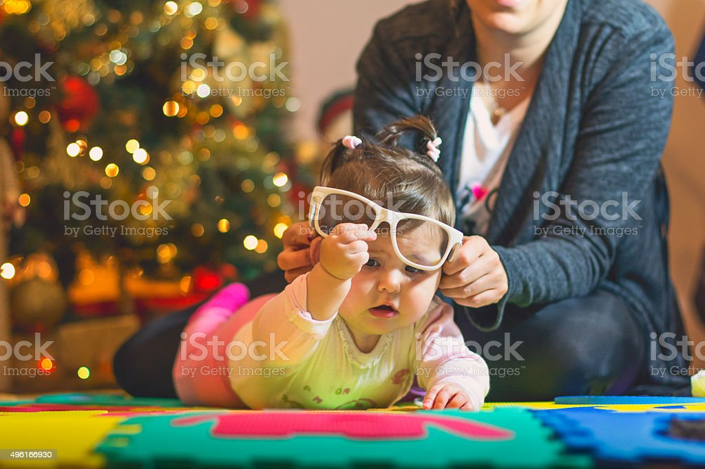mother entertains her  baby girl, on a new year 2016 stock photo