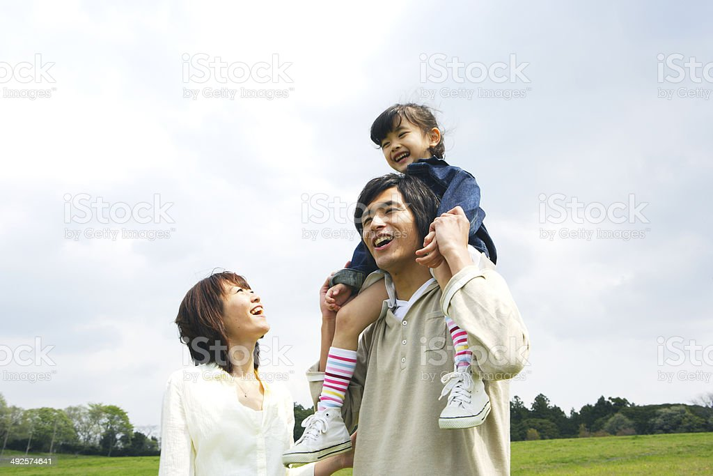 Mother escorting to father with their daughter on his shoulders stock photo