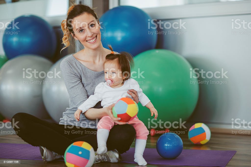Mother exercise with her baby in a gym stock photo