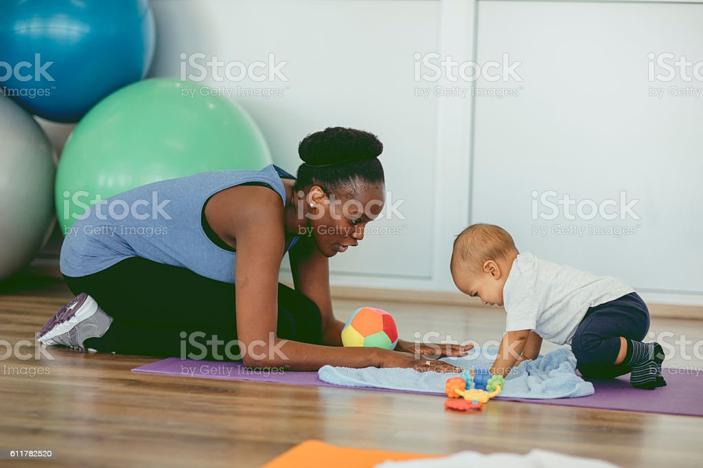 Mother Exercise With Her Baby In a Gym. stock photo