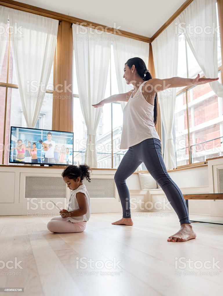 Mother exercising at home stock photo