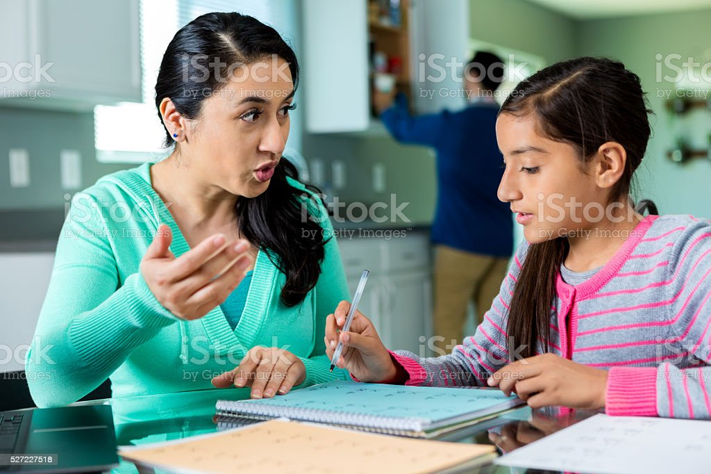 Mother explains math problem to daughter stock photo