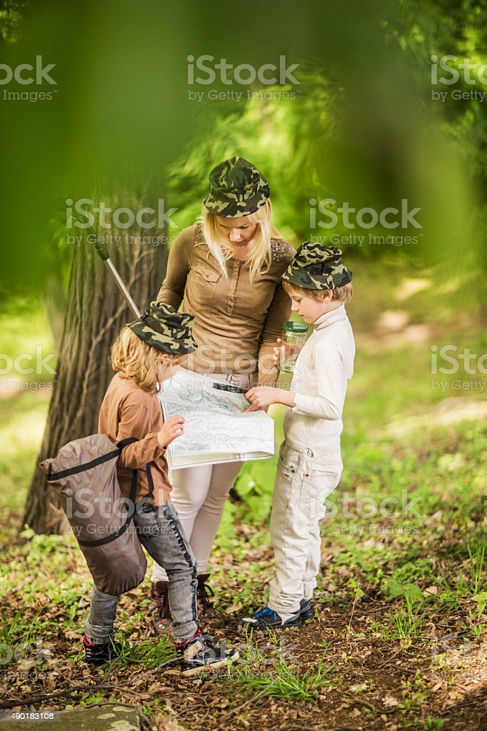 Mother exploring map with her children in nature. stock photo