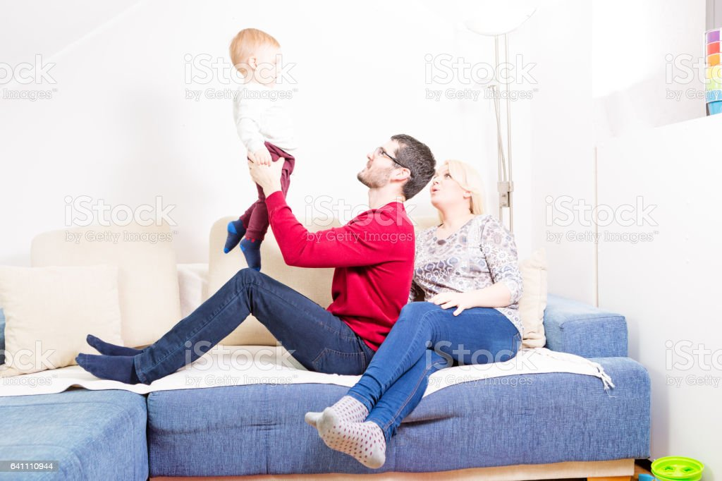 Mother, father and their baby boy playing at home stock photo