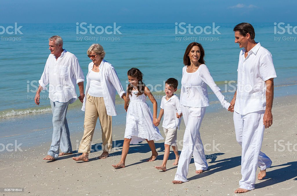 Mother, Father Granparents, Children Family Walking on Beach stock photo
