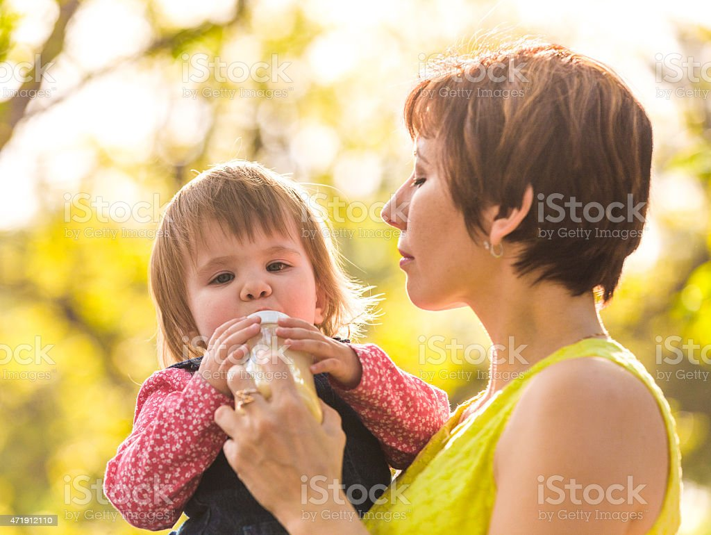 Mother feeding a baby stock photo