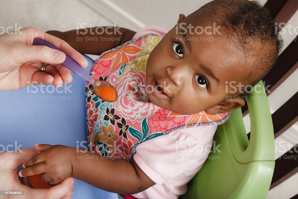 mother feeding adopted baby daughter stock photo