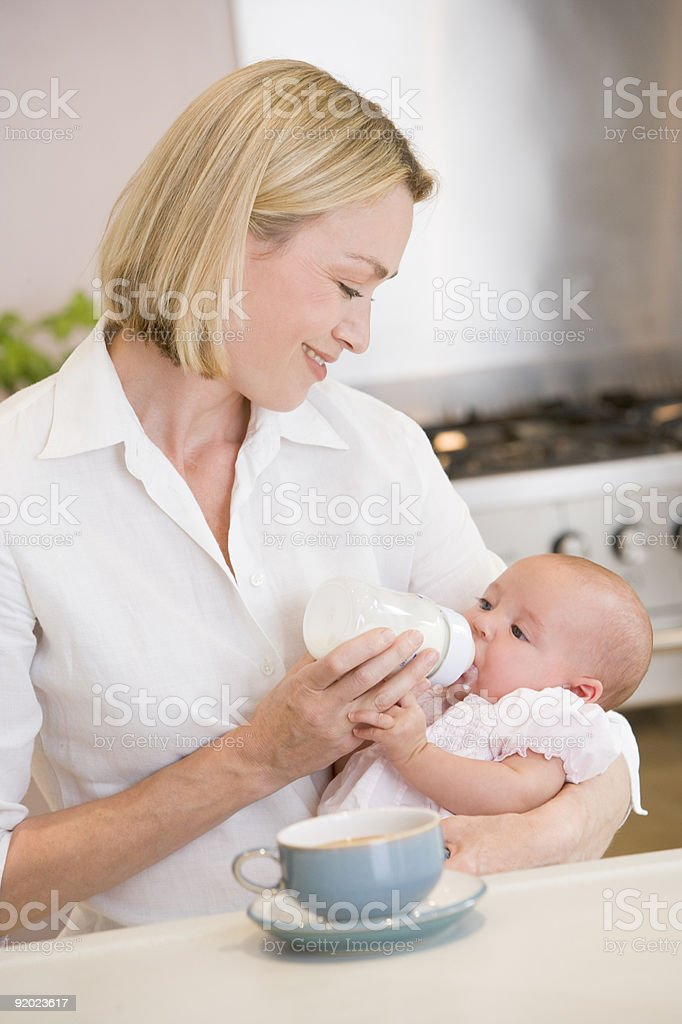 Mother feeding baby in kitchen royalty-free stock photo