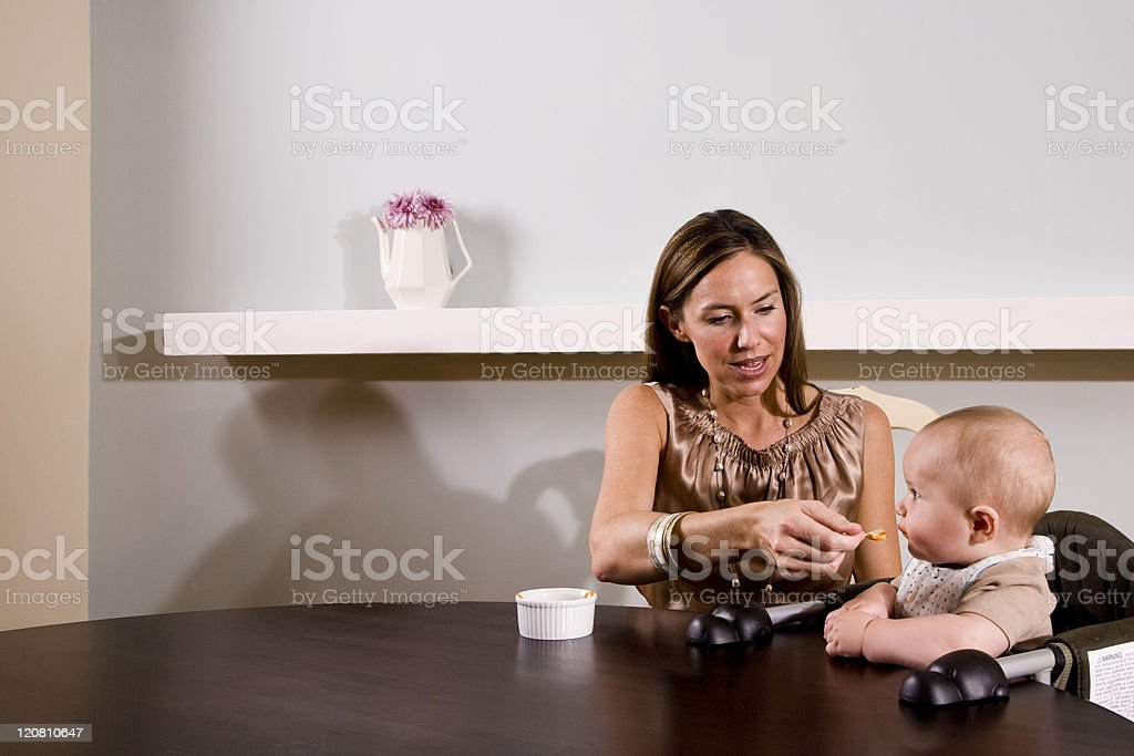Mother feeding baby sitting in high chair royalty-free stock photo