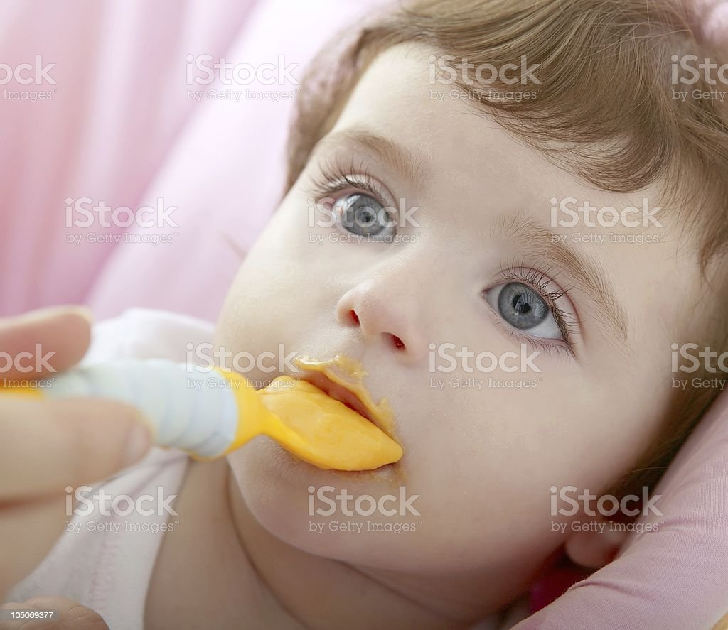 mother feeding baby yellow spoon royalty-free stock photo