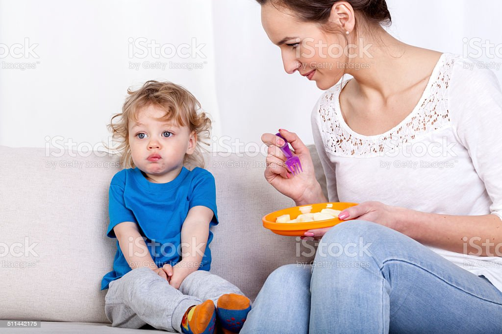 Mother feeding child on couch stock photo