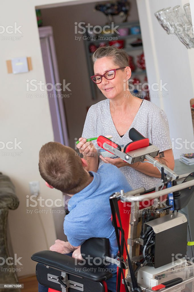 Mother feeding disabled son stock photo