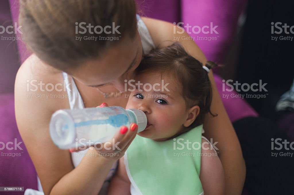 mother feeding her baby girl with milk stock photo