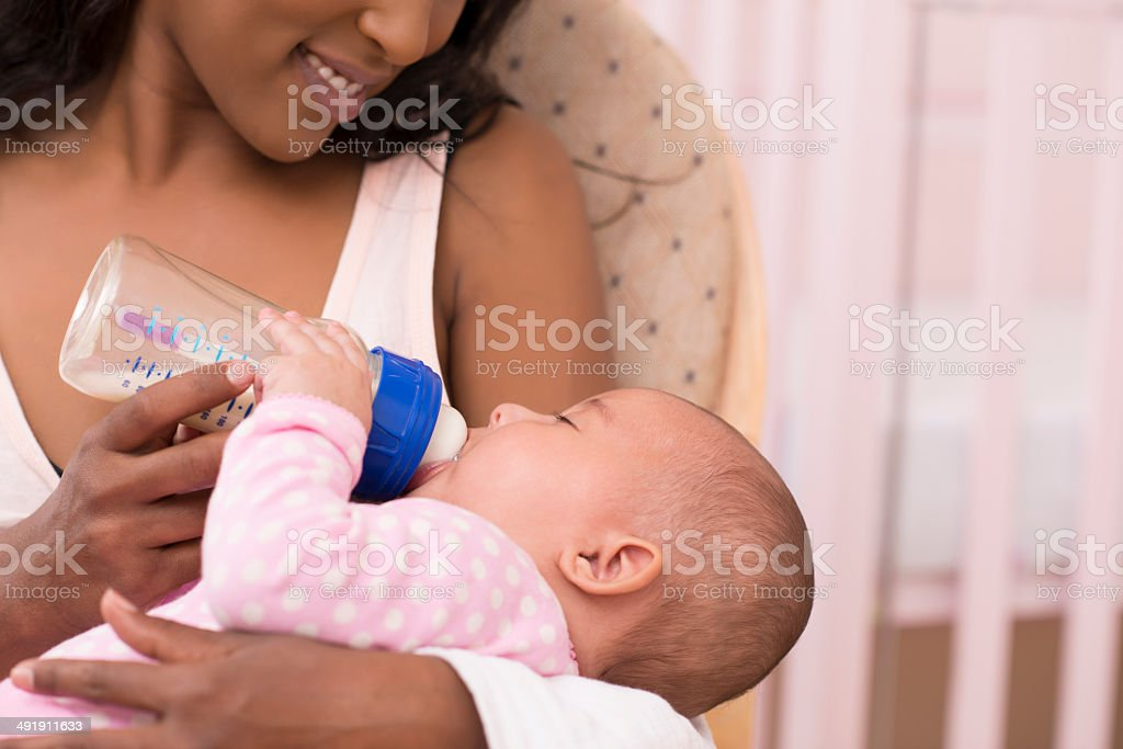 Mother feeding her newborn baby. stock photo
