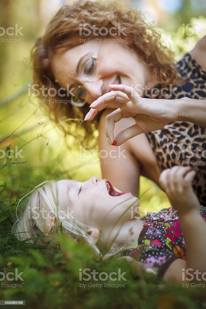 Mother feeding tiny forest strawberry to her little daughter royalty-free stock photo