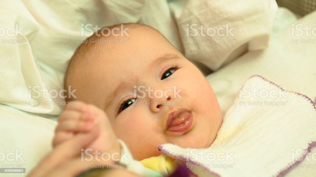 Mother feeds her little child baby puree with spoon stock photo