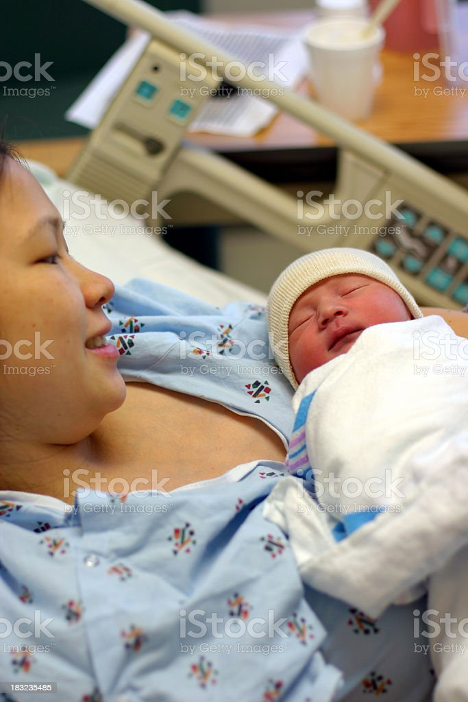Mother gazing lovingly at her newborn baby royalty-free stock photo