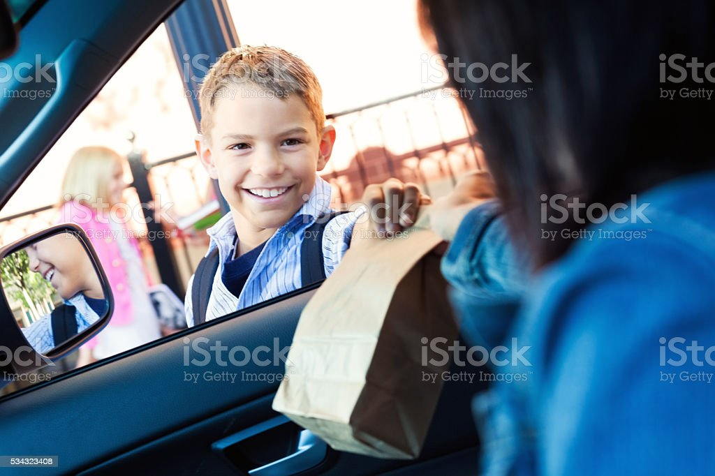 Mother gives son his lunch in carpool line at school stock photo