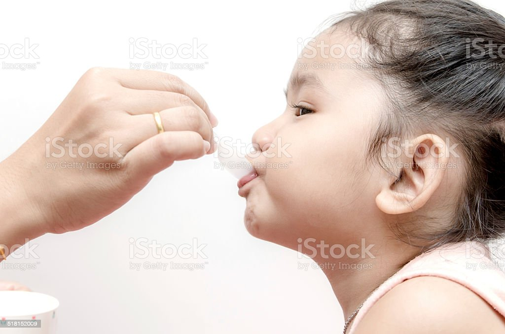 Mother giving  baby girl medicine syrup stock photo