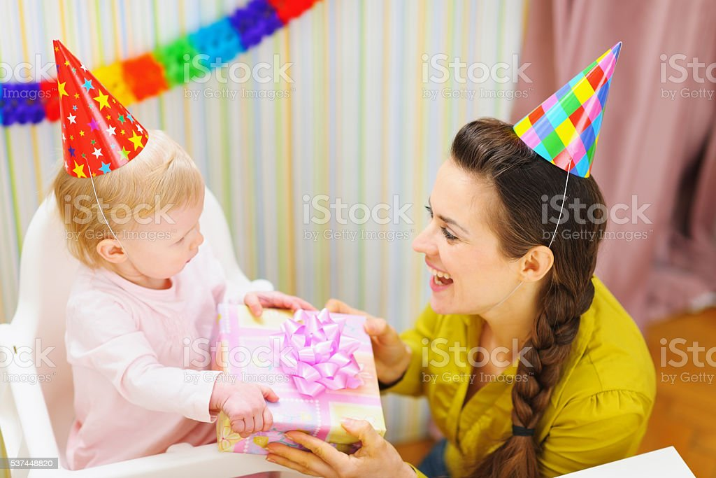 mother giving birthday gift for baby stock photo