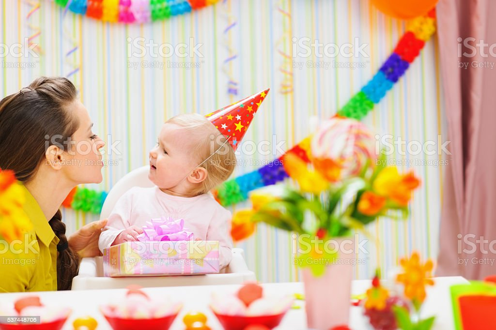 mother giving birthday present for baby stock photo