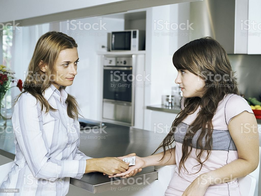 Mother giving condom to daughter stock photo
