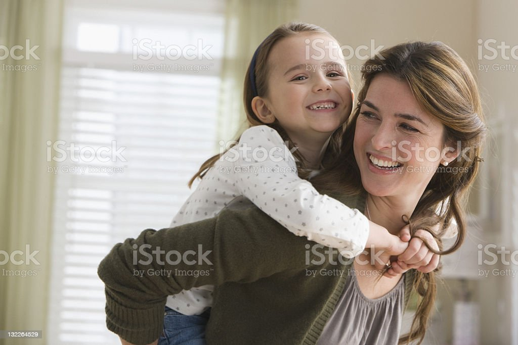 Mother giving daughter piggyback ride royalty-free stock photo