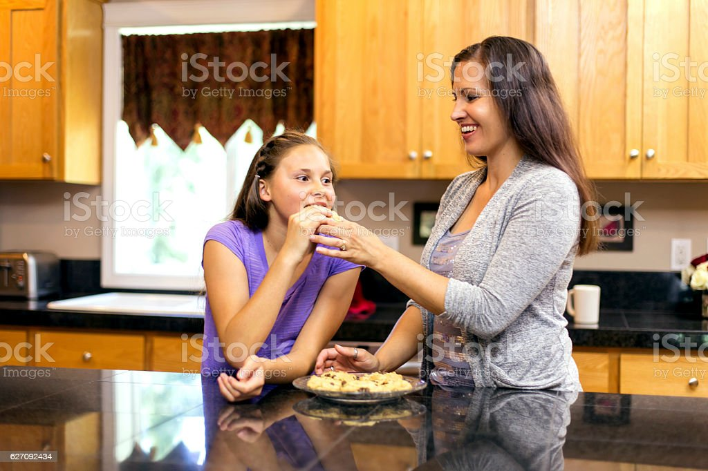 Mother giving her daughter a bike from homemade cookie stock photo